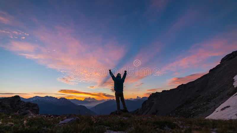 Man standing on mountain top raising arms, sunrise light colorful sky scenis landscape, conquering success leader concept. Man standing on mountain top raising royalty free stock photo