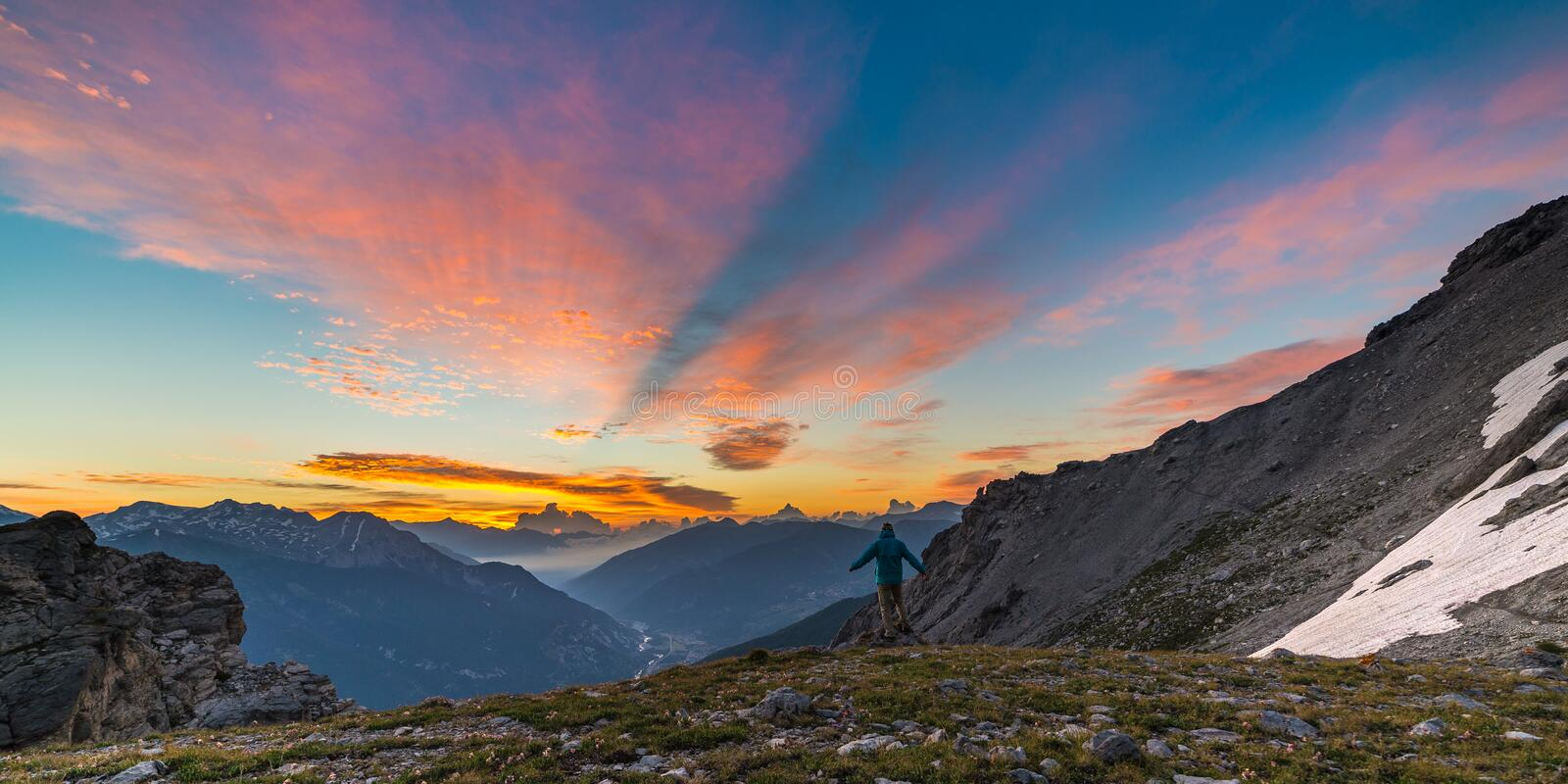 Man standing on mountain top raising arms, sunrise light colorful sky scenis landscape, conquering success leader concept. Man standing on mountain top raising stock image