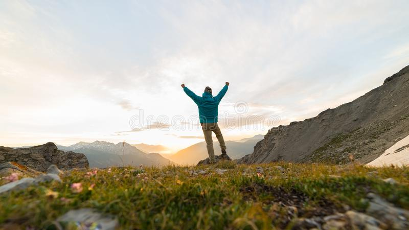 Man standing on mountain top raising arms, sunrise light colorful sky scenis landscape, conquering success leader concept. Man standing on mountain top raising royalty free stock image