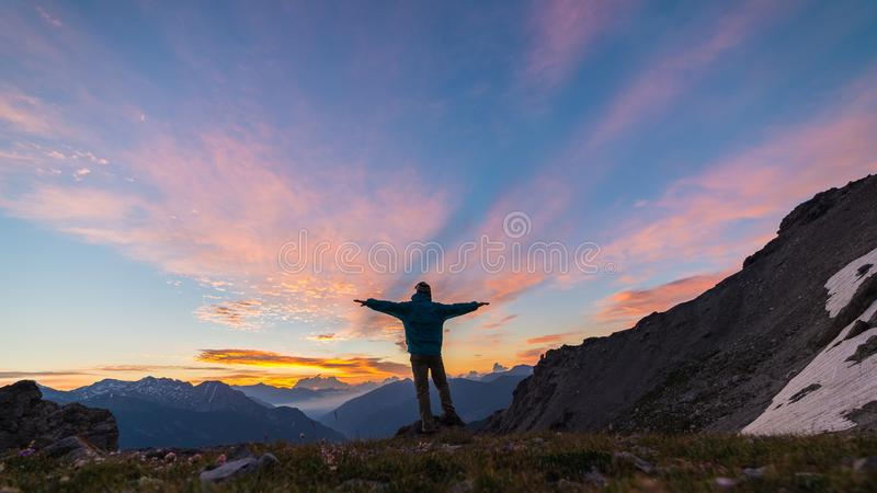 Man standing on mountain top raising arms, sunrise light colorful sky scenis landscape, conquering success leader concept. Man standing on mountain top raising stock photos