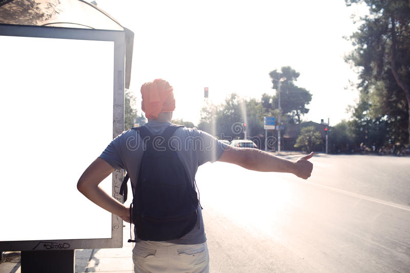 Man standing near bus stop thumbing a lift stock photo