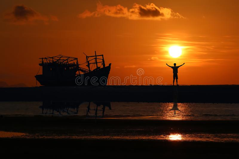 Man standing near the old broken boat abandoned on the beach at sunset stock photo