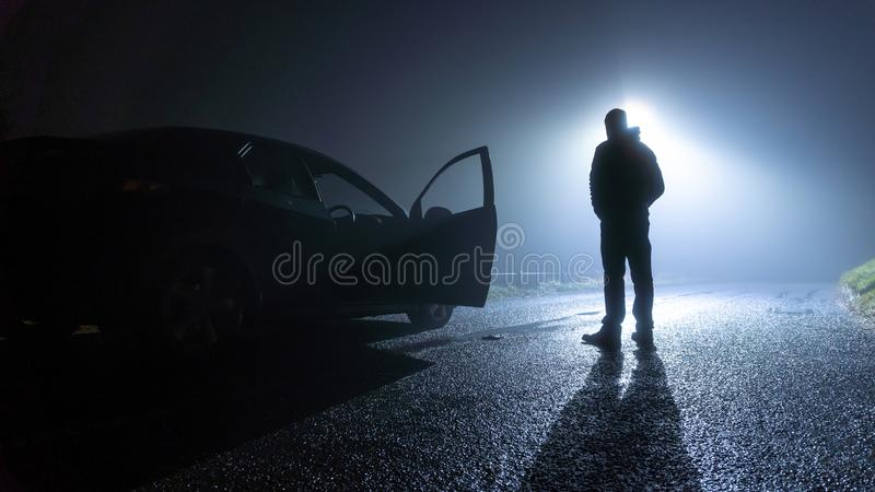 A man standing next to a car, with door open, parked on the side of the road, underneath a street light, on a spooky, scary, rural royalty free stock image