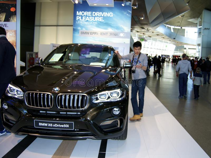 Man standing next to new BMW model. Young man standing besides a new SUV model released by BMW in the showroom royalty free stock photo