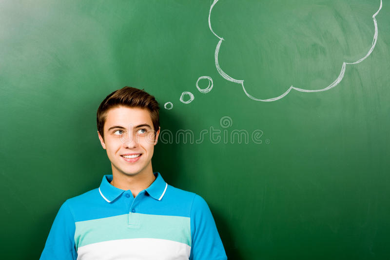 Man standing next to thought bubble on blackboard royalty free stock image