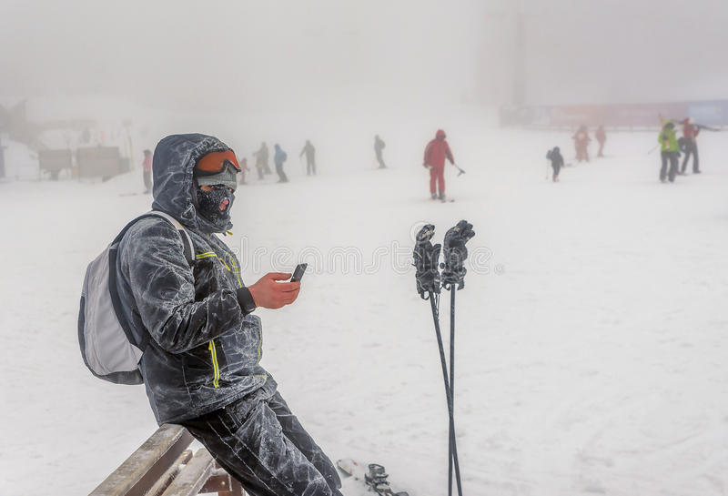Man standing outdoor on the snow and fog and texting on smartphone stock photo