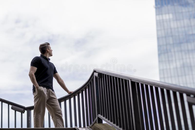 Man Standing on an Outdoor Stairwell and Looking at a Skyscraper. A man standing on an outdoor stairwell holding a handrail and looking towards a skyscraper stock images