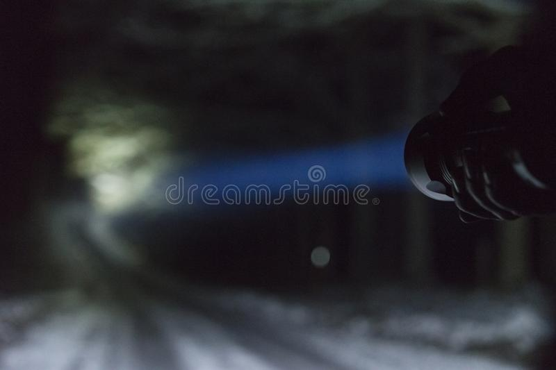 Man standing outdoors at night in Sweden Scandinavia winter landscape shining with flashlight at road. Nice blue light beam. Beautiful, calm and peaceful royalty free stock photography