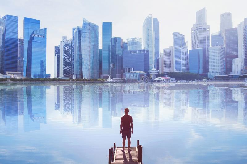 Man standing on the pier looking at modern cityscape skyline royalty free stock photo