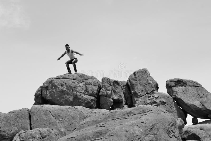 Man standing on pile of rocks -B&W-. Athletic man standing on a pile of rocks in a beautiful site royalty free stock photos