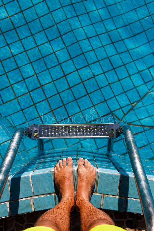Man standing on pool ladder royalty free stock images