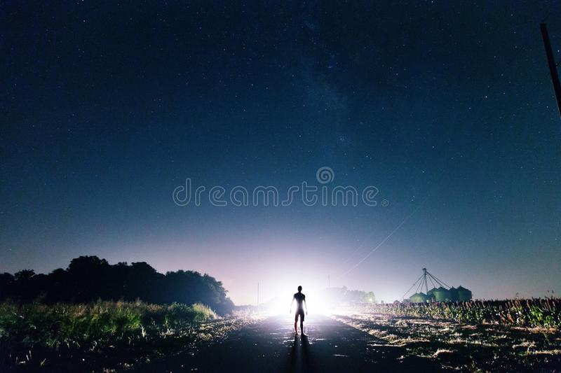 Man Standing on the Road Near Green Grass during Sunrise royalty free stock photography