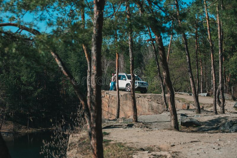 Man standing on rock cliff near white suv car with view on lake. view through trees stock image