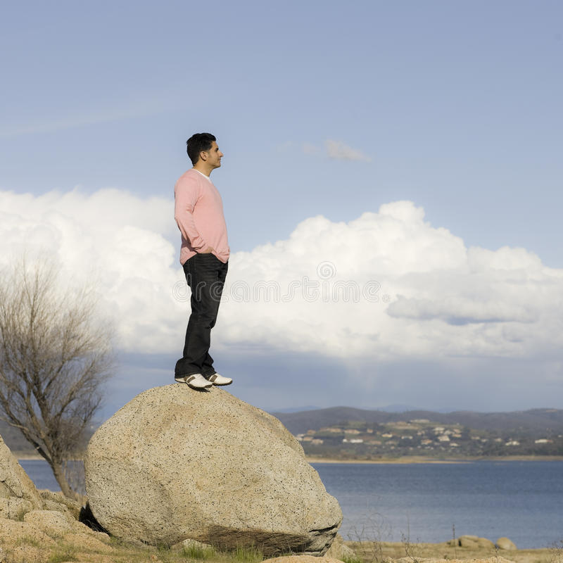Man Standing on Rock Looking into Distance stock photography