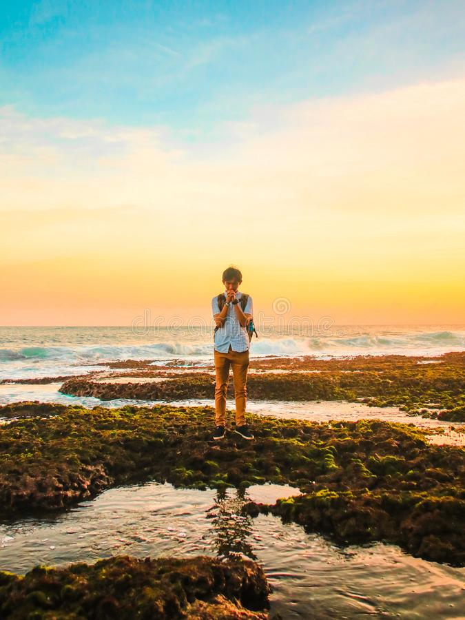 Man Standing on Rocks Near Beach during Golden Hour royalty free stock photo