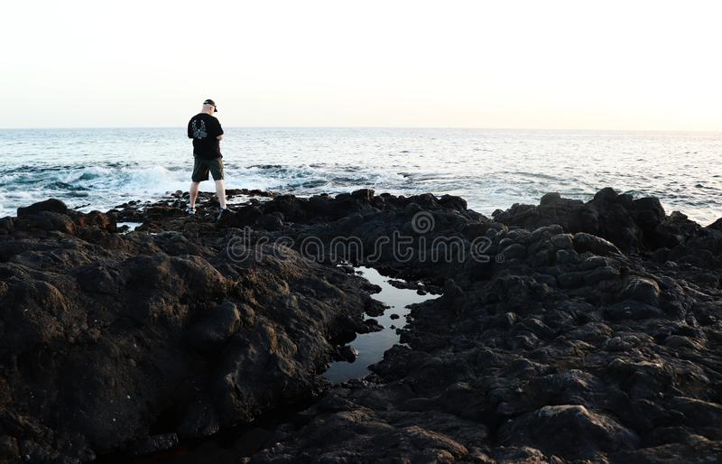 Man standing on rocks at the ocean in Tenerife, Spain royalty free stock photography