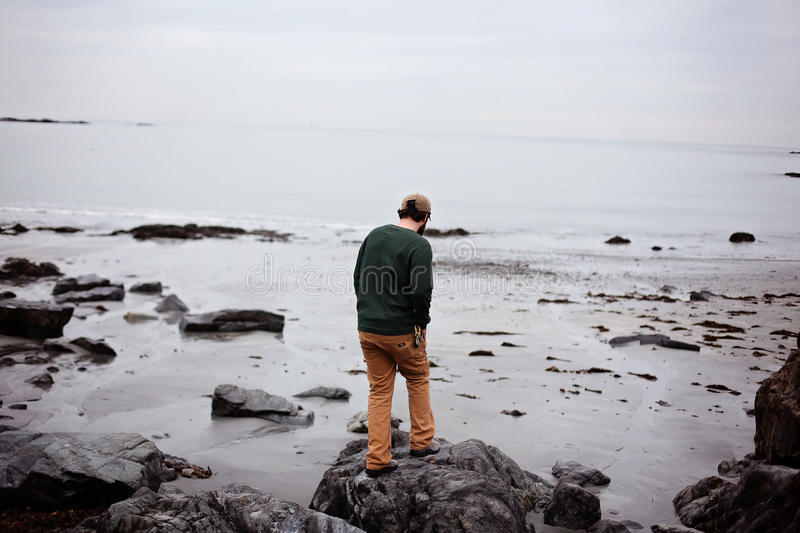 Man standing on rocks at seaside stock photography