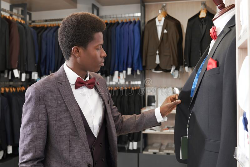 Man standing in shop with clothing near mannequin. royalty free stock photography