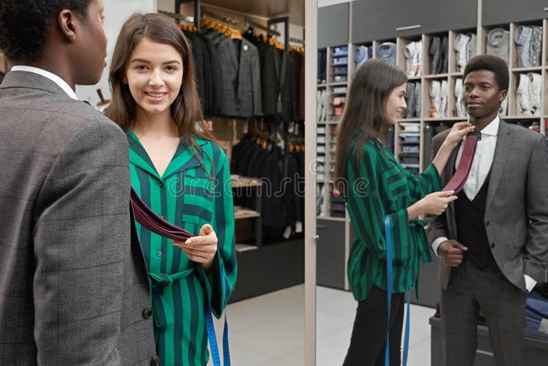 Man standing in shop, looking at mirror, choosing tie. stock photos