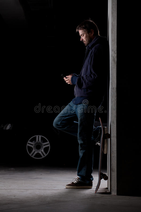 Man standing with skateboard. A man leaning against the wall with a skateboard checking his phone stock photography