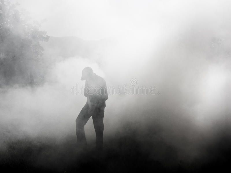 Man standing in smoke. Figure of a man standing in smoke coming from a controlled fire to burn off pest plants royalty free stock photos