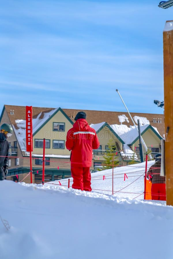 Man standing on a snow covered ground at a ski resort in Park City Utah. An Alternate sign and house under blue sky can also be seen in this winter scenery stock photography