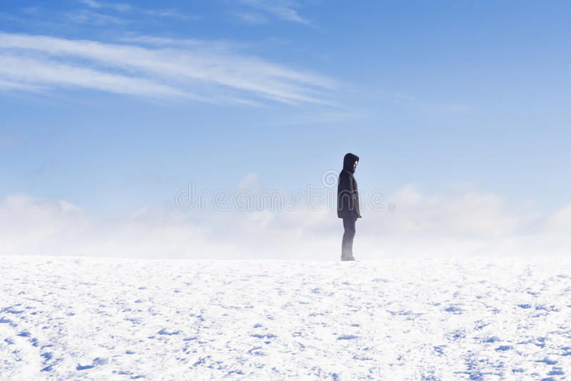 Man standing in snow flurry against blue sky. Man standing on a mountain in snow flurry against blue sky stock images