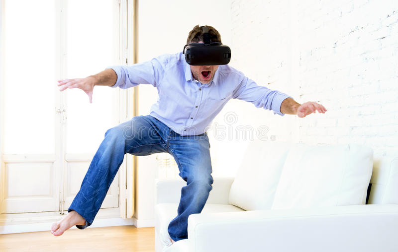Man standing on sofa couch excited using 3d goggles watching 360 virtual reality vision. Young modern man standing at home living room sofa couch playing video royalty free stock photography