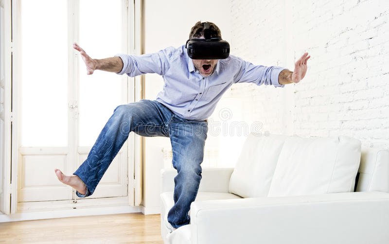 Man standing on sofa couch excited using 3d goggles watching 360. Young modern man at home living room sofa couch playing video game excited using 3d goggles stock photos