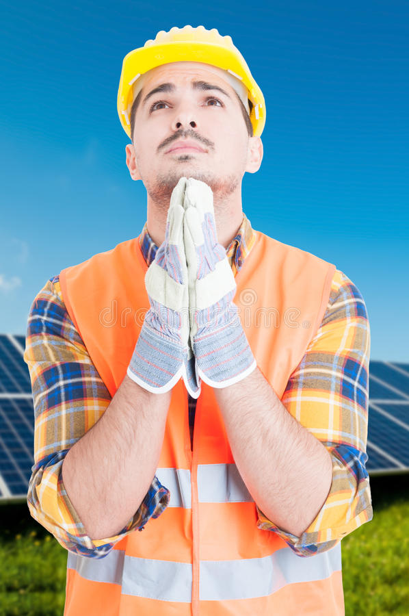 Man standing by solar panels and praying stock image
