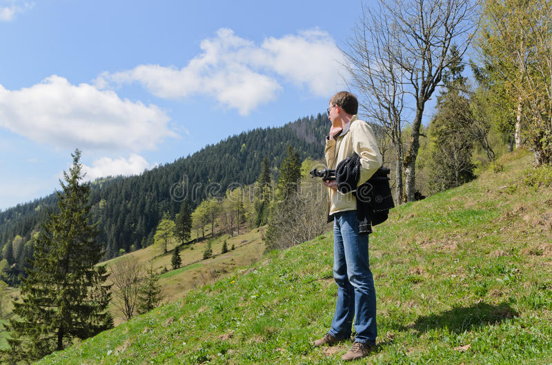 Man standing on a steep grassy stock image