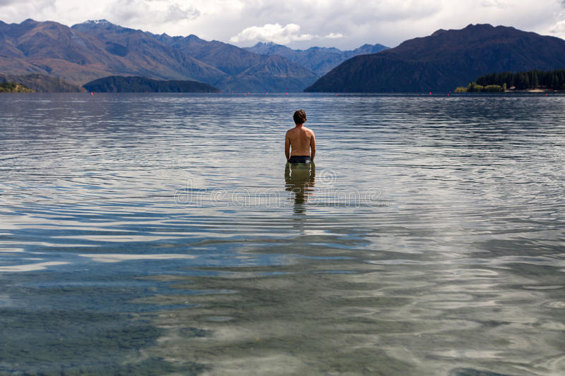 Man standing in still remote lake royalty free stock images