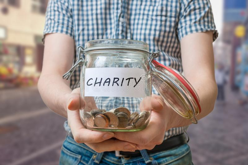 Man standing on street is collecting money for charity and holds jar. With coins royalty free stock photo