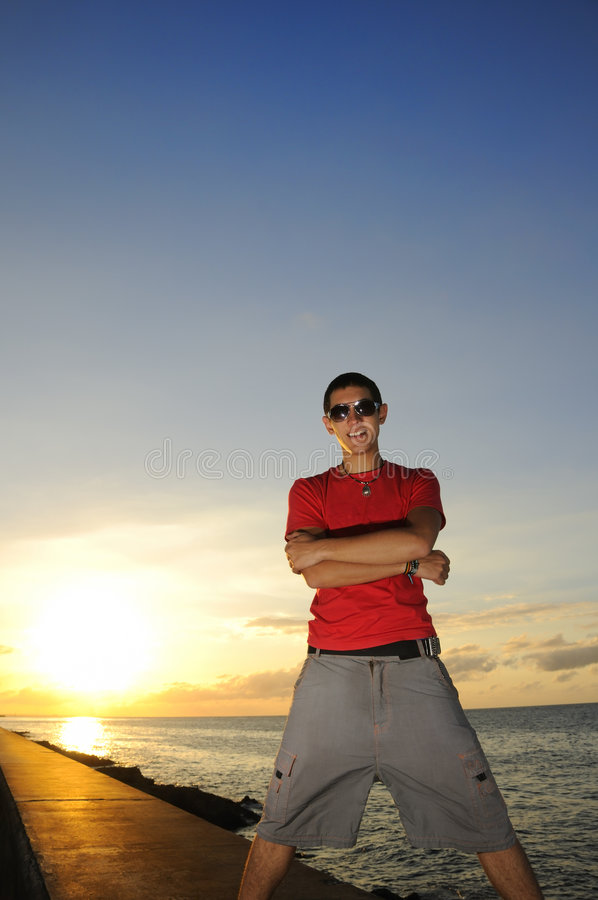 Man standing at sunset. Portrait of young trendy man posing with attitude against sunset sky royalty free stock photos