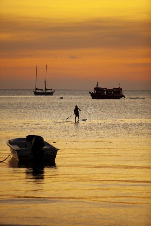 Man standing on sup ,stand up paddle board sailing in koh tao harbor against beautiful sunset sky stock photos
