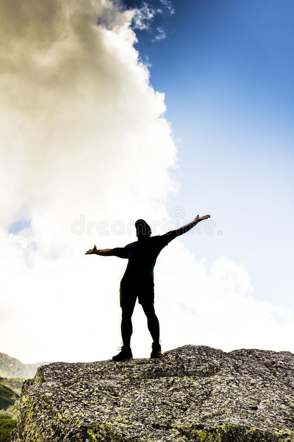 Man standing on top of a cliff with arms raised royalty free stock photos