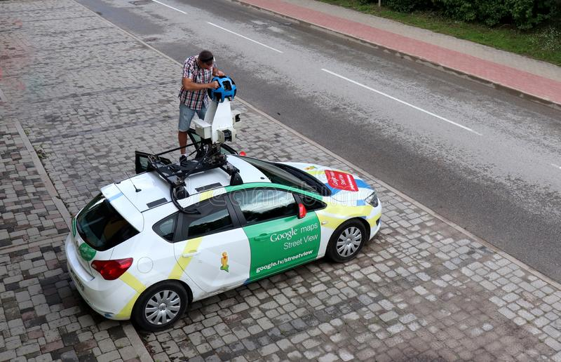 Google Maps Street View car parked in Ikskile, Latvia. Man standing on top of his Google Maps Street View car cleaning the camera in Ikskile, Latvia on a summer royalty free stock images