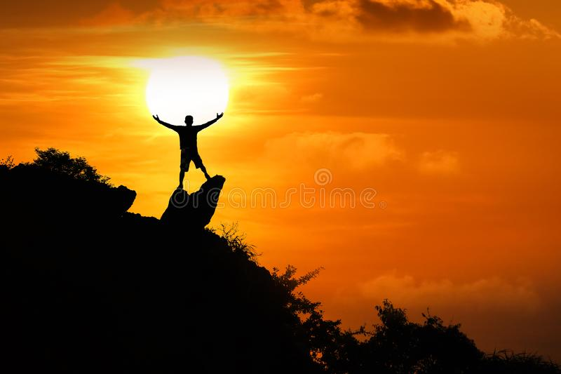 Man standing on the top of the mountain looking at red sky sunset royalty free stock image