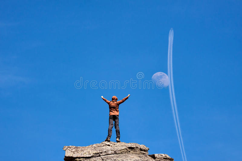 Man standing on the top of the mountain over blue sky with moon stock photography