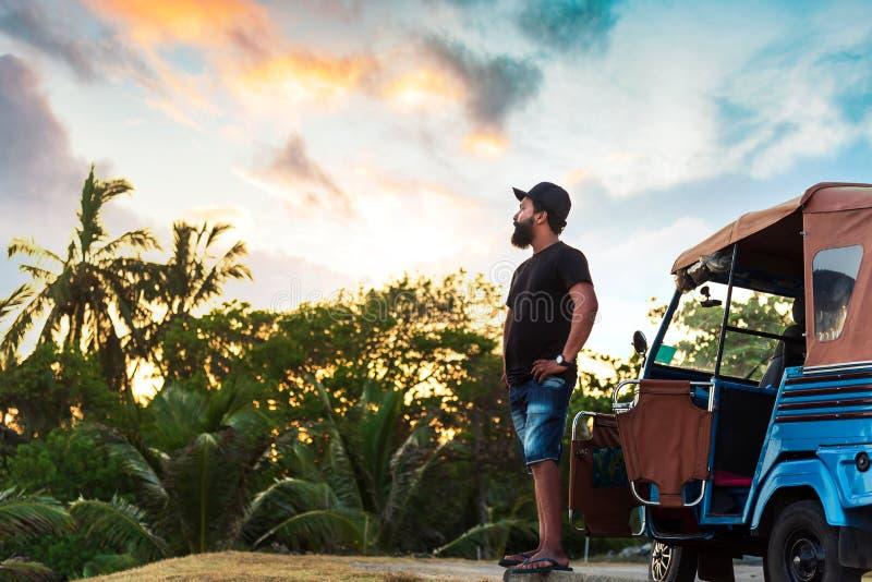 Man standing by the tuk tuk taxi at sunset. Sri Lankan Man standing by the tuk tuk taxi at sunset tuktuk street vehicle asia portrait asian palm rickshaw male stock photos