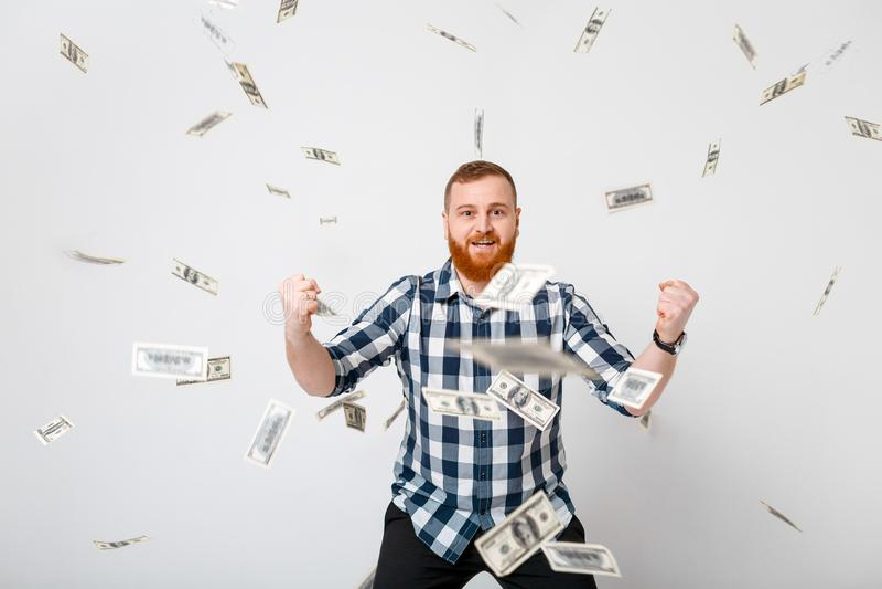 Man standing under money rain. Young handsome happy man with red beard standing under money rain of dollar bills royalty free stock photo