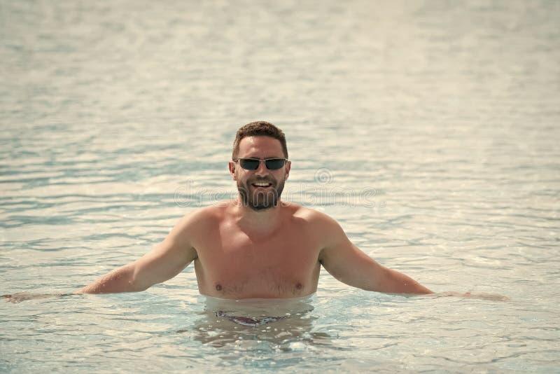 Man standing waist deep in blue sea water stock photo