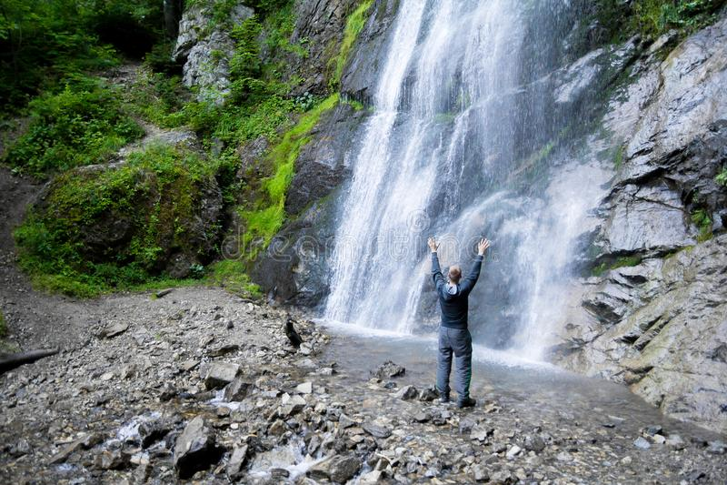 Man standing by waterfalls with arms outstretched in the air stock photography
