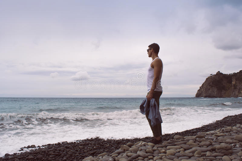 Man standing by the waves of the ocean on a rocky beach. High mountains in the background. Corniglia, Cinque Terre, Liguria, Italy royalty free stock images