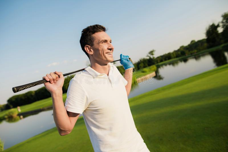 A man in a white suit is standing on a golf course and smiling, holding a golf club behind him royalty free stock photo