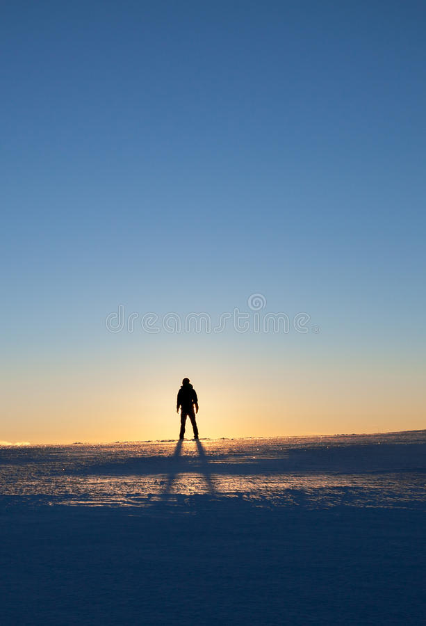 Man standing in winter landscape. Silhouette of man standing in winter landscape stock photography