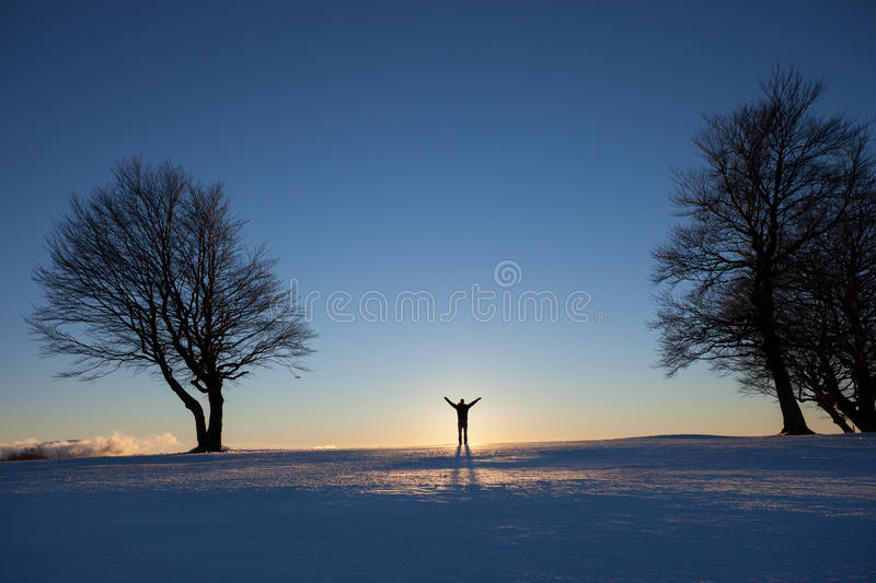 Man standing in winter landscape. Silhouetted man standing in winter landscape stock photo