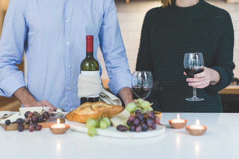 Man Standing Beside Woman Holding Wine Glass in Front of Grapes and Bread on Table royalty free stock photography