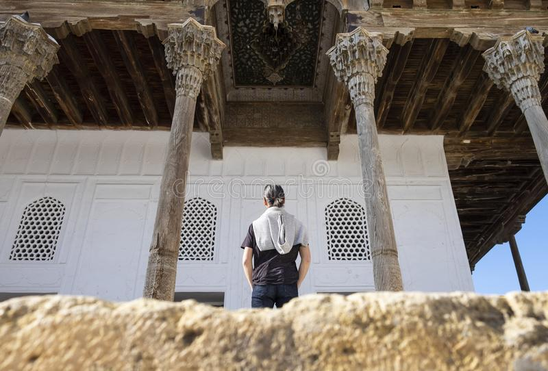 Man standing between wooden columns in inner yard of the ancient Ark of Bukhara, Uzbekistan. Man standing between wooden columns in inner yard of the ancient stock photo