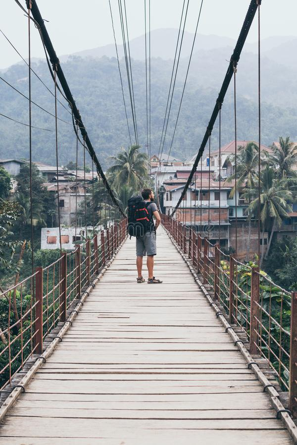Man standing on wooden suspension bridge in a mountain village of Laos stock photos